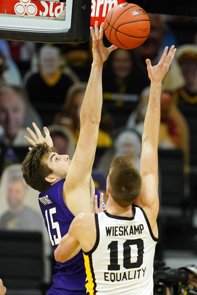 Northwestern center Ryan Young, left, blocks a shot by Iowa guard Joe Wieskamp (10) during the first half of an NCAA college basketball game, Tuesday, Dec. 29, 2020, in Iowa City, Iowa. (AP Photo/Charlie Neibergall)