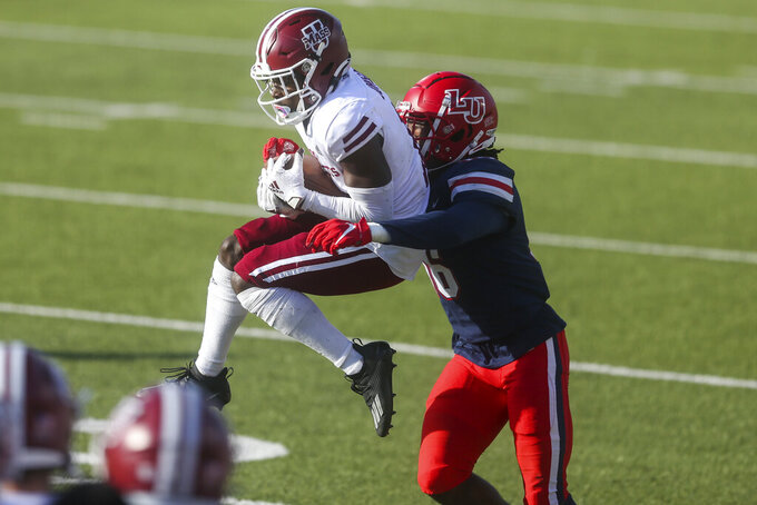 "Massachusetts wide receiver Jermaine ""OC"" Johnson, Jr. (10) makes a catch as he is defended by Liberty cornerback Quinton Reese (16) during the second half of a NCAA college football game on Friday, Nov. 27, 2020, at Williams Stadium in Lynchburg, Va. (AP Photo/Shaban Athuman)"