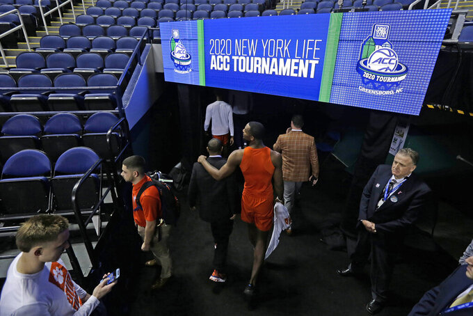 Clemson players leave the floor after the NCAA college basketball games at the Atlantic Coast Conference tournament were canceled due to concerns over the coronavirus in Greensboro, N.C., Thursday, March 12, 2020. (AP Photo/Gerry Broome)