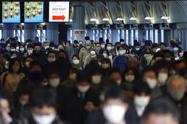 A station passageway is crowded with commuters wearing face mask during a rush hour Friday, Jan. 8, 2021 in Tokyo. Japanese Prime Minister Yoshihide Suga declared a state of emergency Thursday for Tokyo and three other prefectures to ramp up defenses against the spread of the coronavirus. (AP Photo/Eugene Hoshiko)