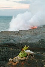 FILE - In this June 22, 2004 file photo, an offering to Pele, goddess of Hawaiian volcanoes, adorns the cliffs above the newest lava flow from Kilauea volcano as it enters the Pacific Ocean at dawn in Volcano, Hawaii. When residents of rural Hawaii neighborhoods where lava from Kilauea volcano has burned down or threatened to consume their homes, a name often comes up: Pele. Pele, known as the goddess of volcanoes and fire, is an important figure in Hawaiian culture. (AP Photo/David Jordan, File)