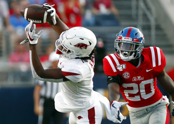 Arkansas wide receiver Trey Knox (7) tries to catch a pass as he is pressured by Mississippi defensive back Keidron Smith (20) during the first half of their NCAA college football game, Saturday, Sept. 7, 2019, in Oxford, Miss. The pass was knocked away by another Mississippi defender. (AP Photo/Rogelio V. Solis)