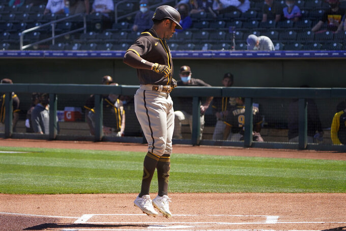 San Diego Padres' Tommy Pham jumps on home plate as he scores on his home run during the first inning of the team's spring training baseball game against the Kansas City Royals, Monday, March 22, 2021, in Surprise, Ariz. (AP Photo/Sue Ogrocki)