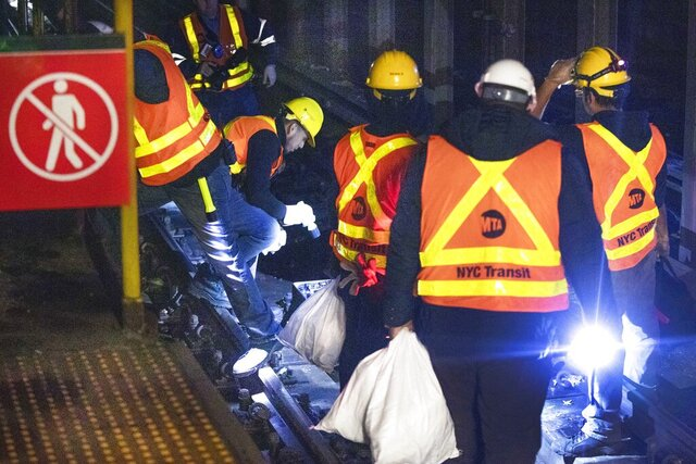 Transit Authority workers carry sandbags on the tracks in a subway station on New York's Upper West Side, Sunday, January 19, 2020. A water main break on Sunday morning flooded city streets on Manhattan's Upper West Side and disrupted subway service, the second one in a week. (AP Photo/Richard Drew)