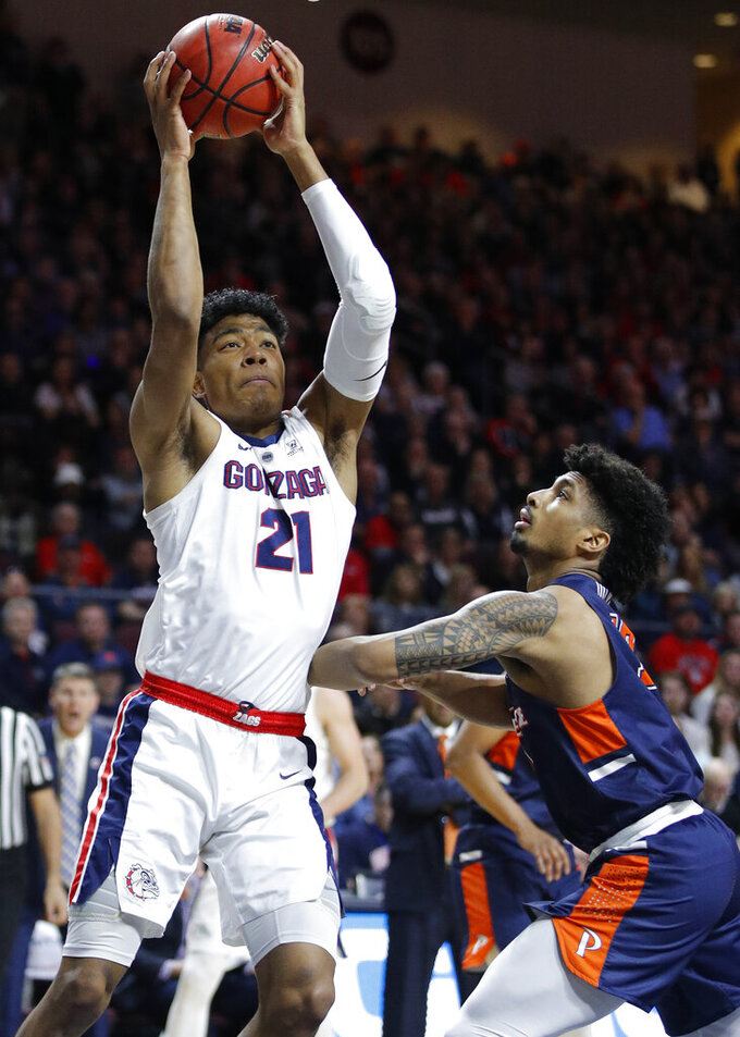 Gonzaga's Rui Hachimura (21) grabs a rebound over Pepperdine's Darnell Dunn during the first half of an NCAA semifinal college basketball game at the West Coast Conference tournament, Monday, March 11, 2019, in Las Vegas. (AP Photo/John Locher)