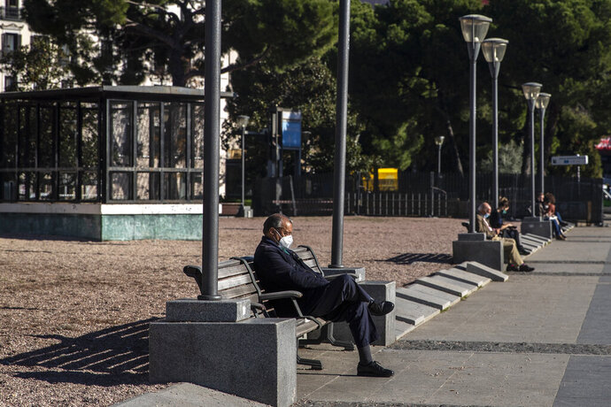 People wearing face masks to prevent the spread of coronavirus sit on a street bench in downtown Madrid, Spain, Monday, Nov. 23, 2020. Spanish Prime Minister Pedro Sanchez says a national COVID-19 vaccination plan will be launched in January. (AP Photo/Manu Fernandez)