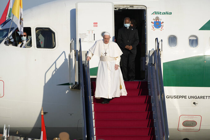 Pope Francis walks down the steps on an airplane as he arrives at Budapest international airport, Sunday, Sept. 12, 2021. Francis is opening his first foreign trip since undergoing major intestinal surgery in July, embarking on an intense, four-day, two-nation trip to Hungary and Slovakia that he has admitted might be overdoing it. (AP Photo/Gregorio Borgia)