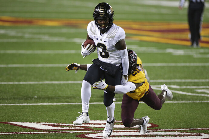Purdue wide receiver David Bell (3) tries to get away from Minnesota defensive back Justus Harris (21) during the first half of an NCAA college football game Friday, Nov. 20, 2020, in Minneapolis. (AP Photo/Stacy Bengs)