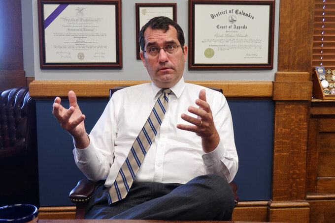 Kansas Attorney General Derek Schmidt answers questions during an Associated Press interview in his office, Thursday, July 23, 2020, in Topeka, Kan. Schmidt says he believes both counties and local school districts can opt out of Gov. Laura Kelly's order requiring K-12 schools to have staff and students wear masks. (AP Photo/John Hanna)