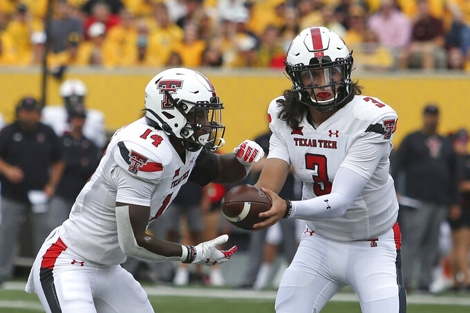Texas Tech quarterback Henry Colombi (3) hands the ball to running back Xavier White (14) during the first half of an NCAA college football game against West Virginia in Morgantown, W.Va., Saturday, Oct. 2, 2021. (AP Photo/Kathleen Batten)