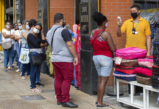 People line up to get their temperatures checked before entering a store in a downtown shopping district of Sao Paulo, Brazil, Wednesday, June 10, 2020. Retail shops reopened on Wednesday in Brazil's biggest city after a two-month coronavirus pandemic shutdown that aimed to contain the spread of the new coronavirus. (AP Photo/Andre Penner)