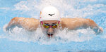 Japanese swimmer Rikako Ikee competes on way to winning the women's 100-meter butterfly at the Japan's national championships at Tokyo Aquatics Centre in Tokyo, Sunday, April 4, 2021.  Ikee on Sunday qualified for the Tokyo Olympics just two years after the was diagnosed with leukemia. (Kyodo News via AP)