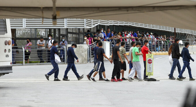 Several immigrants are escorted off an immigration bus on the Hidalgo International Bridge on Wednesday, June, 2, 2021 in Hidalgo, Texas. The congressional delegation from Texas and Arizona got a tour of the Texas-Mexico border in the Rio Grande Valley to get an update on the migrant surge in the region. (Delcia Lopez/The Monitor via AP)