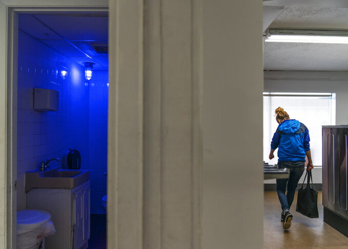 "A blue light illuminates the bathroom in the Cookie Carnival laundromat to make it harder for drug users to find a vein in Huntington, W.Va, Thursday, March 18, 2021. The laundromat was among several local businesses to install blue lights at the height of the city's opioid crisis, when they would often find syringes left behind by drug users. ""It was the only thing we could think of to do to help,"" said manager Misti Mann-France. ""And it has helped tremendously."" She said people have overdosed several times in the parking lot of their business. ""I wish there was a solution to the bigger problem,"" she said. ""There are so many out there on drugs, and it's sad, it really is."" (AP Photo/David Goldman)"