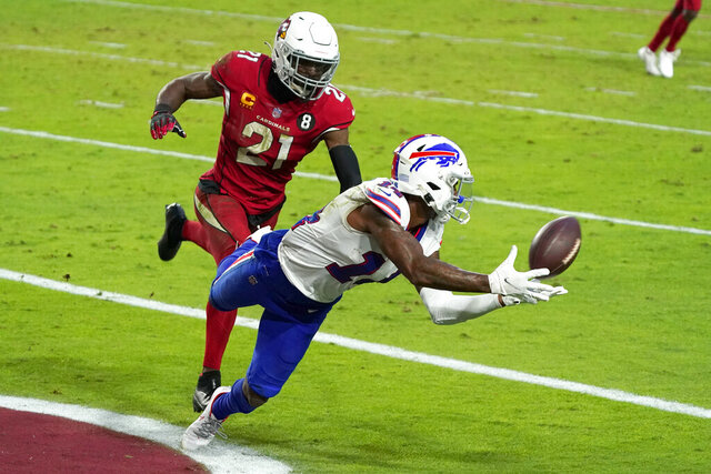 FILE - In this Sunday, Nov. 15, 2020, file photo Buffalo Bills wide receiver Stefon Diggs (14) pulls in a touchdown pass as Arizona Cardinals cornerback Patrick Peterson (21) defends during the second half of an NFL football game in Glendale, Ariz. Painted rightly or wrongly as yet another one of the NFL's many diva receivers for his various sideline outbursts during his first five seasons in Minnesota, Diggs has put behind his mercurial past by quickly warming up to his new surroundings. (AP Photo/Rick Scuteri, File)