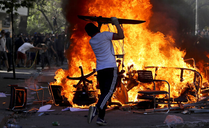 "An anti-government protester adds an object to burning chairs and benches amid a march by students and union members in Santiago, Chile, Monday, Oct. 21, 2019. Protesters defied an emergency decree and confronted police in Chile's capital on Monday, continuing disturbances that have left at least 11 dead and led the president to say the country is ""at war."" (AP Photo/Miguel Arenas)"