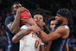 Georgetown center Qudus Wahab, left, and and guard Jagan Mosely, right, struggle to control the ball at the expense of Texas forward Gerald Liddell (0) during the second half of the first round of the 2K Empire Classic NCAA college basketball tournament, Thursday, Nov. 21, 2019, in New York. Georgetown defeated Texas 82-66. (AP Photo/Kathy Willens)