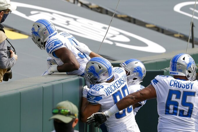 Detroit Lions' Kerryon Johnson does a Lambeau Leap after running for a touchdown during the first half of an NFL football game against the Green Bay Packers Sunday, Sept. 20, 2020, in Green Bay, Wis. (AP Photo/Mike Roemer)