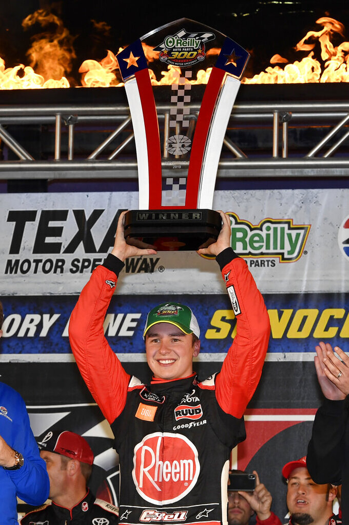 Christopher Bell holds the trophy in Victory Lane as he celebrates his win in the NASCAR Xfinity Series auto race at Texas Motor Speedway in Fort Worth, Texas, Saturday, Nov. 2, 2019. (AP Photo/Larry Papke)