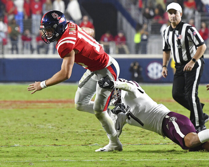 Texas A&M defensive back Devin Morris (7) tackles Mississippi quarterback John Rhys Plumlee (10) during the second half of an NCAA college football game in Oxford, Miss., Saturday, Oct. 19, 2019. (AP Photo/Thomas Graning)