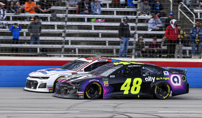 Jimmie Johnson (48) passes Alex Bowman (88) for the lead during a NASCAR Cup Series auto race at Texas Motor Speedway, Sunday, Nov. 3, 2019, in Fort Worth, Texas. (AP Photo/Larry Papke)