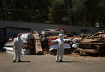 An employee of Xochimilco's crematorium directs a hearse into the unloading area, as him and another employee wait for the corpse of a person suspected to have died of the new coronavirus, in Mexico City, Monday, May 4, 2020. The men are standing next to pile of discarded coffins that contained people who died of COVID-19 disease, and are waiting to be destroyed at the site. (AP Photo/Fernando Llano)