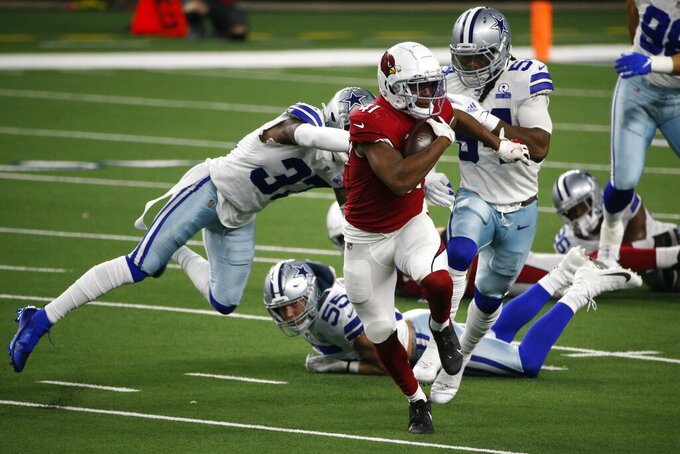 Arizona Cardinals running back Kenyan Drake (41) breaks past Dallas Cowboys' Donovan Wilson (37), Leighton Vander Esch (55) and Jaylon Smith (54) for a long run in the second half of an NFL football game in Arlington, Texas, Monday, Oct. 19, 2020. (AP Photo/Michael Ainsworth)