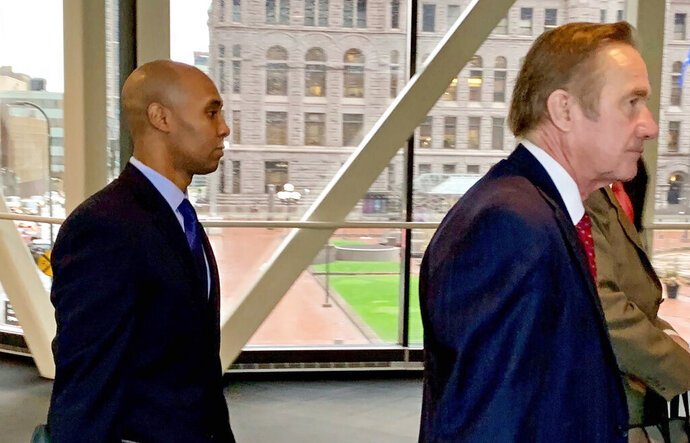 Former Minneapolis police officer Mohamed Noor, left, arrived with his defense attorneys Peter Wold, center, and Thomas Plunkett, right, partially hidden, on April 17, 2019, before another day of testimony in Noor's murder and manslaughter trial in Minneapolis. Noor is accused of fatally shooting an unarmed woman, Justine Ruszczyk Damond, on July 15, 2017, after she called 911 to report a possible sexual assault near her home. (AP Photo/Jeff Baenen)