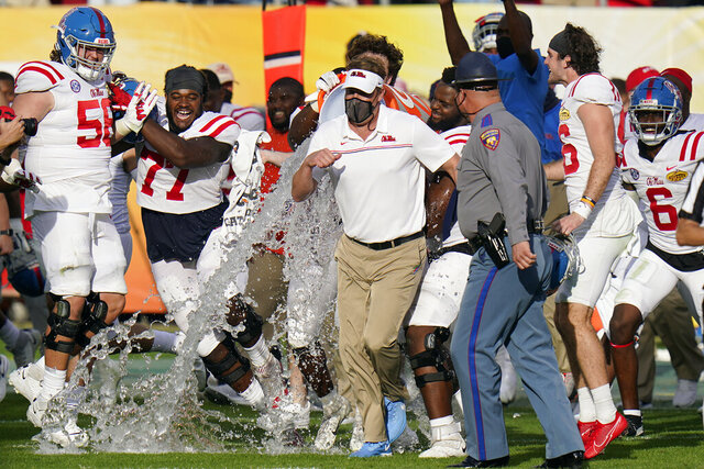 Mississippi head coach Lane Kiffin, center, runs to avoid getting doused with water by his team after the team defeated Indiana during the Outback Bowl NCAA college football game Saturday, Jan. 2, 2021, in Tampa, Fla. (AP Photo/Chris O'Meara)