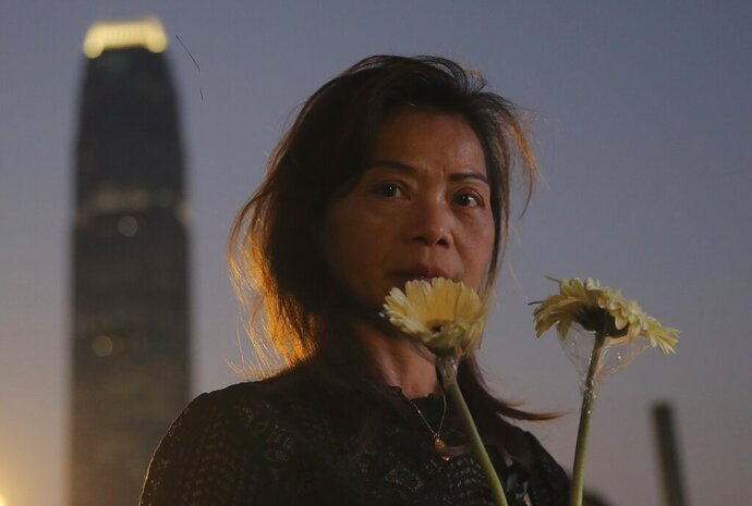 A woman attends a vigil for student Chow Tsz-Lok in Hong Kong, Saturday, Nov. 9, 2019. Chow Tsz-Lok, the Hong Kong university student who fell off a parking garage after police fired tear gas during clashes with anti-government protesters died Friday in a rare fatality in five months of unrest, fueling more outrage against authorities in the semi-autonomous Chinese territory. (AP Photo/Kin Cheung)