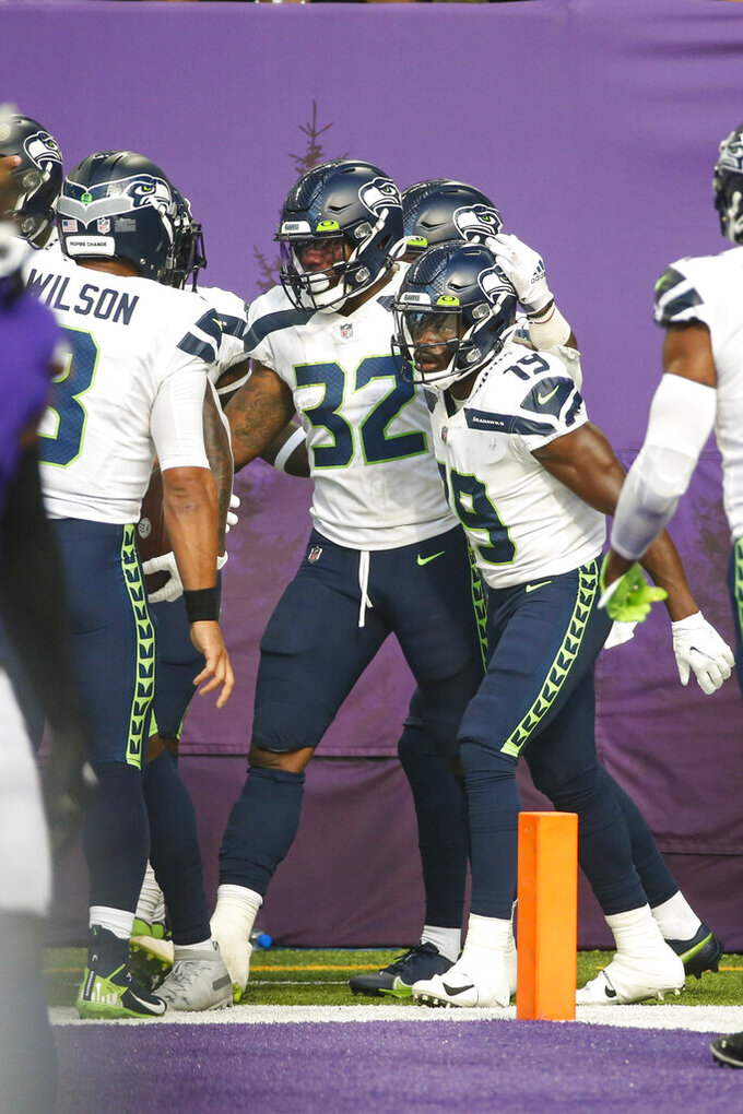 Seattle Seahawks running back Chris Carson (32) celebrates a touchdown with wide receiver Penny Hart (19) and quarterback Russell Wilson (3) in the first half of an NFL football game in Minneapolis, Sunday, Sept. 26, 2021. (AP Photo/Bruce Kluckhohn)