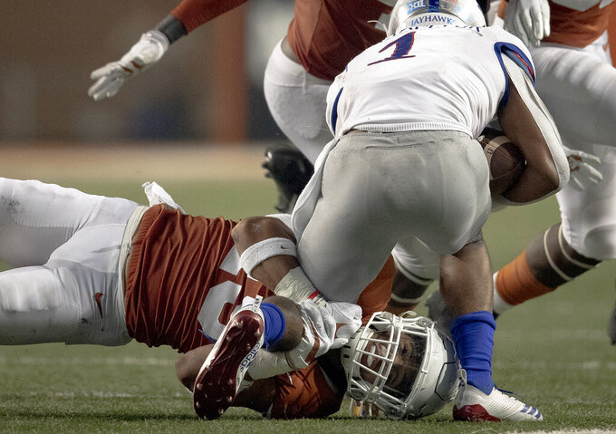 Texas defensive back Brandon Jones (19) wraps up Kansas running back Pooka Williams Jr. (1) during an NCAA college football game Saturday, Oct. 19, 2019, in Austin, Texas. (Nick Wagner/Austin American-Statesman via AP)