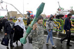 An Iranian teenager carries a mock rocket propelled grenade, during a rally marking the 40th anniversary of the 1979 Islamic Revolution, in Tehran, Iran, Monday, Feb. 11, 2019. Hundreds of thousands of Iranians poured out onto the streets of Tehran and other cities and towns across the country, marking the date 40 years ago that is considered victory day in the country's 1979 Islamic Revolution. (AP Photo/Ebrahim Noroozi)