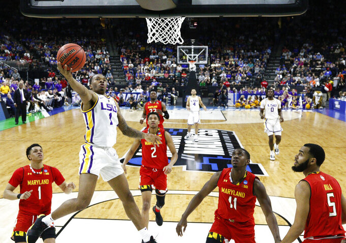 LSU's Javonte Smart (1) goes up for a shot past Maryland players, from left, Anthony Cowan Jr. (1), Aaron Wiggins (2), Darryl Morsell (11) and Eric Ayala (5) during the first half of a second-round game in the NCAA men's college basketball tournament in Jacksonville, Fla., Saturday, March 23, 2019. (AP Photo/Stephen B. Morton)