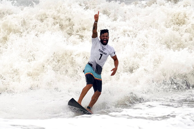 Brazil's Italo Ferreira celebrates wining the gold medal in the men's surfing competition at the 2020 Summer Olympics, Tuesday, July 27, 2021, at Tsurigasaki beach in Ichinomiya, Japan. (AP Photo/Francisco Seco)