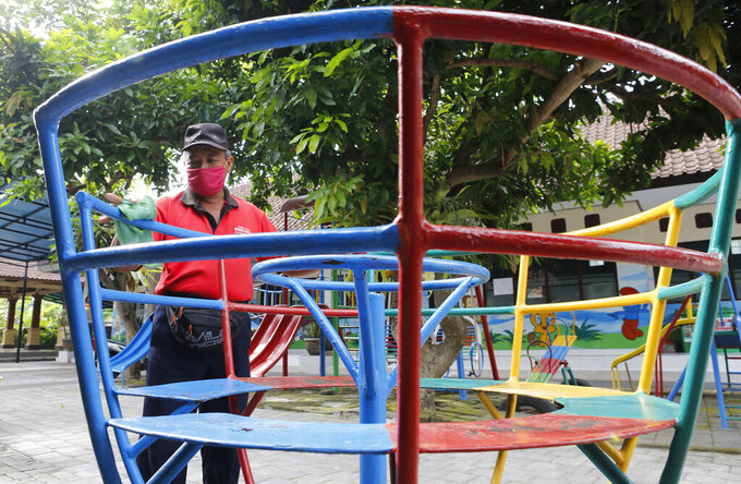 A worker wears a face mask for curbing the spread of coronavirus outbreak at an empty school ground in Bali, Indonesia on Monday, Nov. 23, 2020. (AP Photo/Firdia Lisnawati)