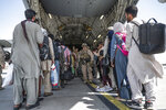 In this Aug. 21, 2021, image provided by the U.S. Air Force, U.S. Airmen and U.S. Marines guide evacuees aboard a U.S. Air Force C-17 Globemaster III in support of the Afghanistan evacuation at Hamid Karzai International Airport in Kabul, Afghanistan. (Senior Airman Brennen Lege/U.S. Air Force via AP)