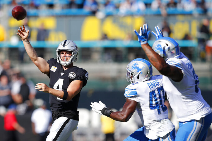 Oakland Raiders quarterback Derek Carr (4) passes as he is pressured by Detroit Lions middle linebacker Jarrad Davis (40) and defensive tackle A'Shawn Robinson during the first half of an NFL football game in Oakland, Calif., Sunday, Nov. 3, 2019. (AP Photo/John Hefti)