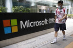 A man wearing a mask walks past the Microsoft office in Beijing, China on Friday, Aug. 7, 2020. U.S. President Donald Trump on Thursday ordered a sweeping but unspecified ban on dealings with the Chinese owners of consumer apps TikTok and WeChat, although it remains unclear if he has the legal authority to actually ban the apps from the U.S. Earlier in the week, Trump threatened a deadline of Sept. 15 to