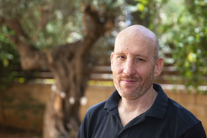 Israeli software developer Itamar Lev poses for a photograph at his house in the central Israeli city of Kfar Saba, Thursday, June 4, 2020. At first, when the coronavirus broke out, Lev was told to work from home. Then his salary was slashed 20%, his dining allowance was taken away and a long-term savings fund frozen. That's the harsh truth facing workers laid off around the world, from software companies in Israel to restaurants in Thailand and car factories in France, whose livelihoods fell victim to a virus-driven recession that's accelerating decline in struggling industries and upheaval across the global workforce. (AP Photo/Sebastian Scheiner)