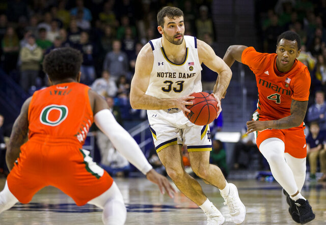 Notre Dame's John Mooney (33) looks to pass between Miami's Chris Lykes (0) and Keith Stone (4) during the second half of an NCAA college basketball game Sunday, Feb. 23, 2020, in South Bend, Ind. (AP Photo/Robert Franklin)