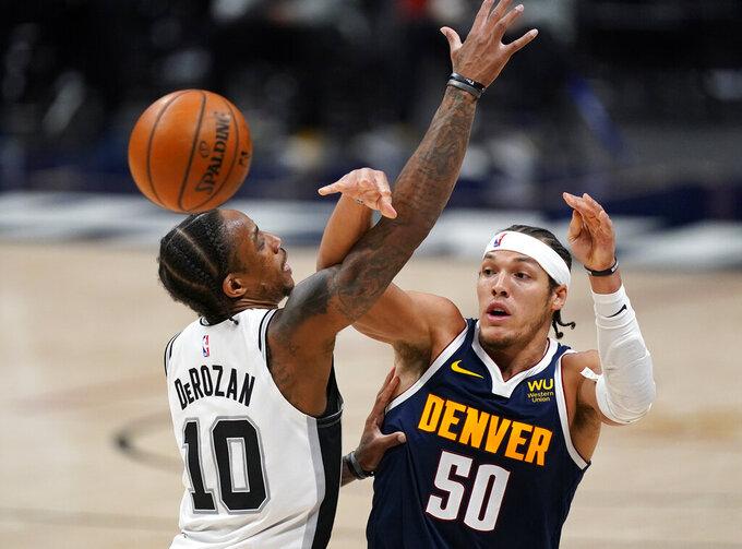 Denver Nuggets forward Aaron Gordon, right, passes the ball as San Antonio Spurs forward DeMar DeRozan defends in the second half of an NBA basketball game Friday, April 9, 2021, in Denver. (AP Photo/David Zalubowski)