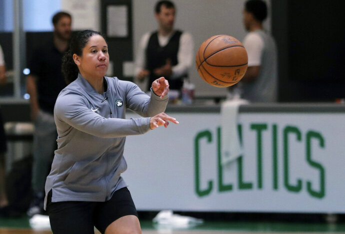 "FILE - In this July 1, 2019, file photo, Boston Celtics assistant coach Kara Lawson passes the ball at the team's training facility in Boston. Celtics guard Gordon Hayward said Lawson has already made her presence felt. ""She's been good as far as just the experience she has as a basketball player,"" Hayward said. ""Reading the game and kind of little things she sees coaching on the sideline. Having somebody that well-versed in basketball, that experience is good."" (AP Photo/Charles Krupa, File)"