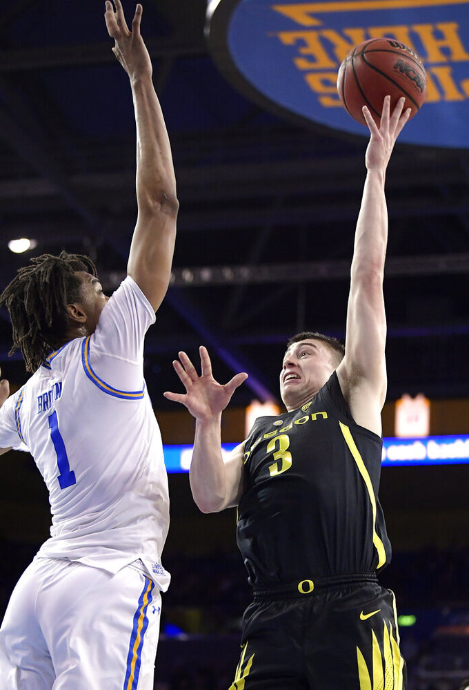 Oregon guard Payton Pritchard, right, shoots as UCLA center Moses Brown defends during the first half of an NCAA college basketball game Saturday, Feb. 23, 2019, in Los Angeles. (AP Photo/Mark J. Terrill)