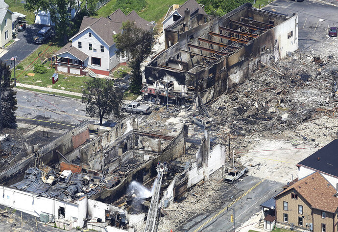 In a view looking northwest from above, the aftermath of a gas explosion in downtown Sun Prairie, Wis., is seen Wednesday, July 11, 2018. At the top right of the image is the site of the former Barr House where the explosion originated and leveled the building. Sun Prairie Fire Department Capt. Cory Barr was killed Tuesday when a natural gas explosion leveled most of a city block, including the tavern Barr owned. (John Hart/Wisconsin State Journal via AP)