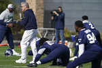 Seattle Seahawks head coach Pete Carroll, left, claps his hands as players stretch before NFL football practice, Wednesday, Oct. 13, 2021, in Renton, Wash. (AP Photo/Ted S. Warren)