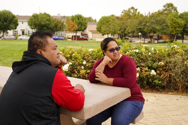 Makerita Iosefo-Va'a and her husband Shaun Va'a sit together in a park near a relative's home where they are temporarily staying in Tracy, Calif., on Oct. 8, 2020. The couple are homesick for American Samoa. She's among an estimated 600 residents of the U.S. territory who were away when American Samoa's governor closed borders to keep the cluster of Pacific islands free from coronavirus. Vaʻa and others say they don't want American Samoa to open its borders, but just to bring them home safely. (AP Photo/Eric Risberg)