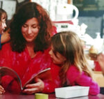 This photo provided by Tara Reade shows Tara Reade reading a book with her seven-year-old daughter at her daughter's school in Seattle, in 2001. (Tara Reade via AP)