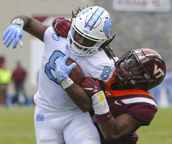 North Carolina's Michael Carter (8) is tackled from behind by Virginia Tech defender Devon Hunter (7) in the second quarter of an NCAA college football game Saturday, Oct. 19 2019, in Blacksburg Va. (Matt Gentry/The Roanoke Times via AP)