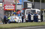 FILE - In this March 15, 2019, file photo, police stand outside a mosque in Linwood, Christchurch, New Zealand. New Zealand police on Wednesday, April 17, 2019 released a detailed timeline of their response to the March 15 shootings that left 50 dead at two Christchurch mosques, confirming they arrested the suspected shooter 18 minutes after receiving the first emergency call. (AP Photo/Mark Baker, File)